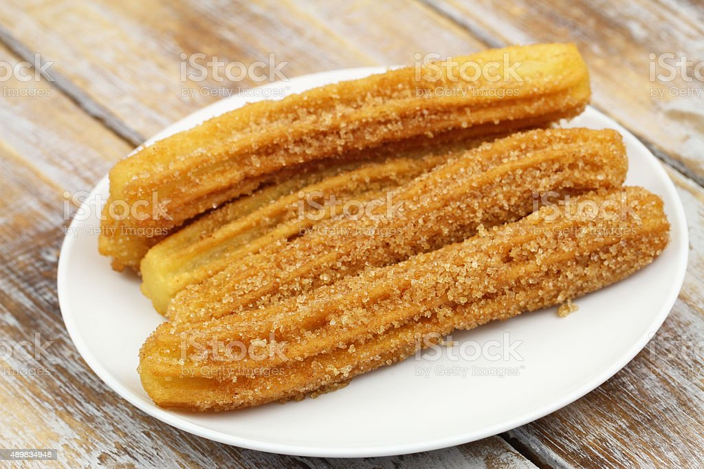 Churros on white plate on rustic wooden surface stock photo