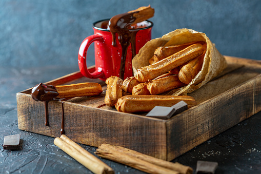 Wooden tray with traditional spanish churros dessert and mug of hot chocolate on a textured dark background, selective focus.