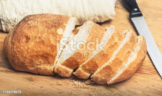 Ciabatta bread loaf slices on wooden board with knife. Fresh crusty white wheat bread Italian cuisine