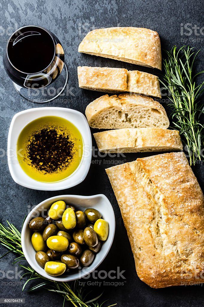 Ciabatta, pepper oil, olives, arugula, rosemary, slate background - foto de acervo