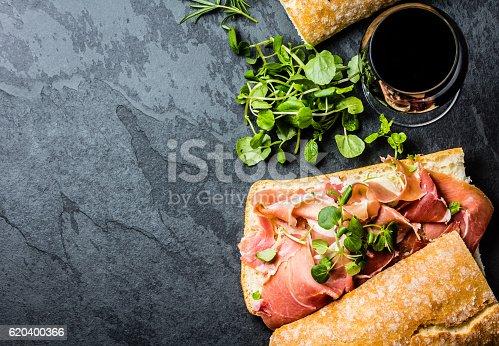 istock Ciabatta sandwich with jamon ham, arugula, red wine, slate background 620400366