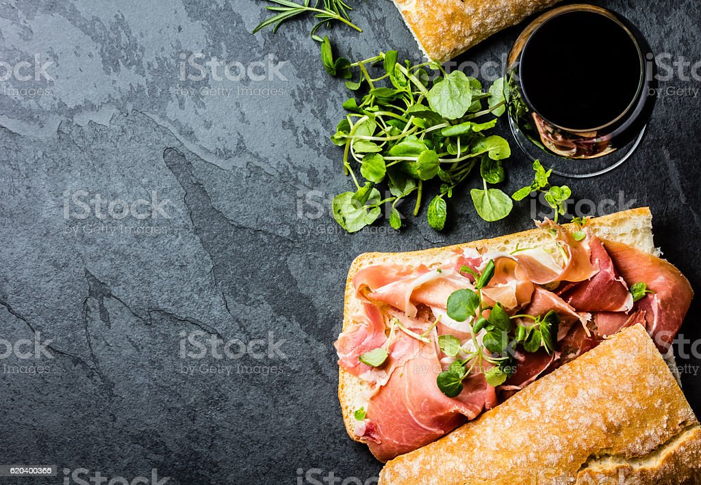 Ciabatta sandwich with jamon ham, arugula, red wine, slate background stock photo
