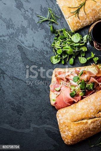 istock Ciabatta sandwich with jamon ham, arugula, slate background 620705704