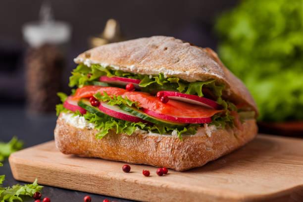 ciabatta-sandwich mit lachs, gemüse und frischem salat auf hölzernen boarde - gemüselaibchen stock-fotos und bilder