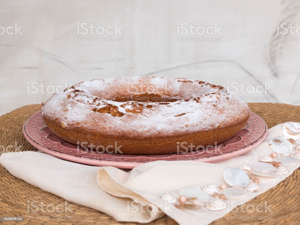 Ciambellone sprinkled with powdered sugar on pink ceramic plate. Plate resting on a napkin decorated with fragments of nacre on bamboo table. stock photo