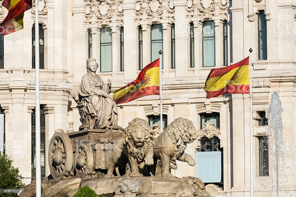 Cibeles Fountain in Madrid and Spanish flags stock photo