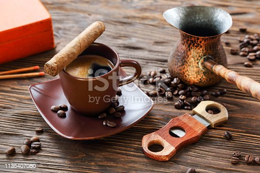 Cigar and a cup of black coffee on a wooden table