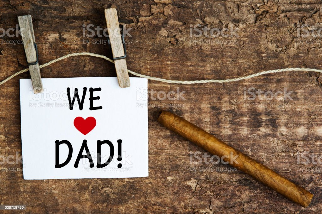 cigar and white sign with the words We Love Dad – Foto