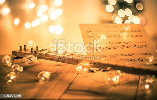istock Cigar box guitar with instrumental sheet music and soft lights for Christmas holiday, split tone 1080273936