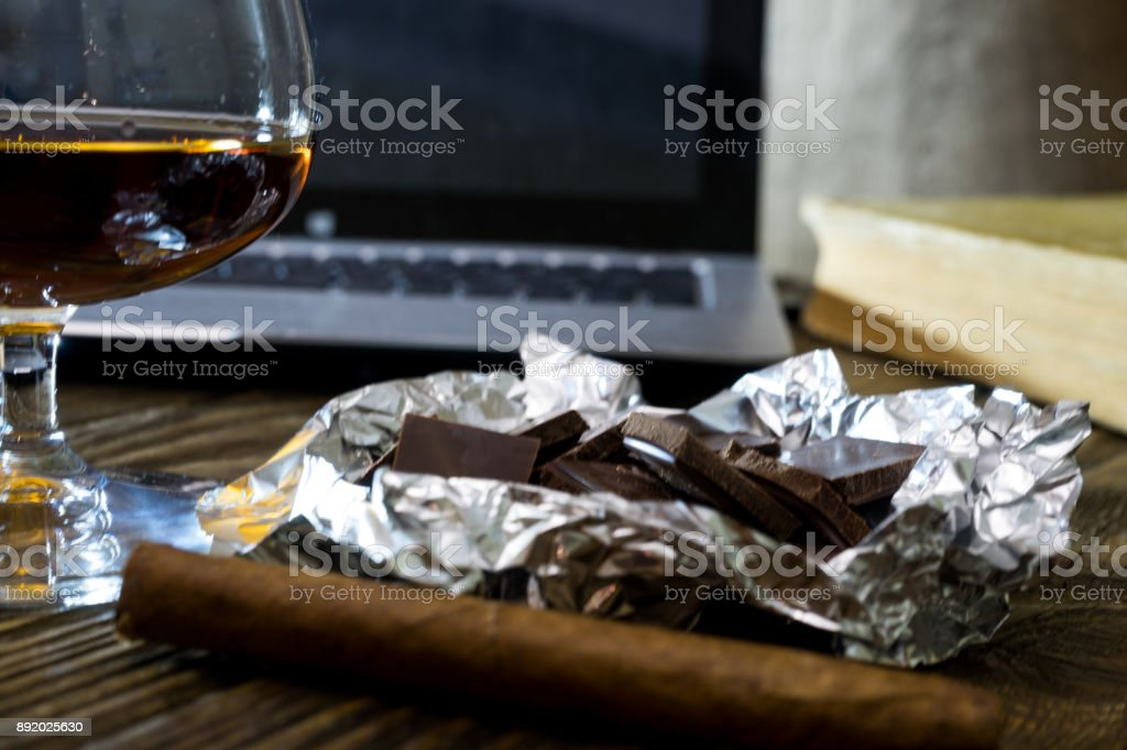 Cigar, glass of cognac, a broken chocolate, a laptop, and an old folio on textured oak table stock photo