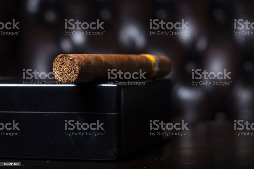 Cigar on black box has brown leather in background stock photo