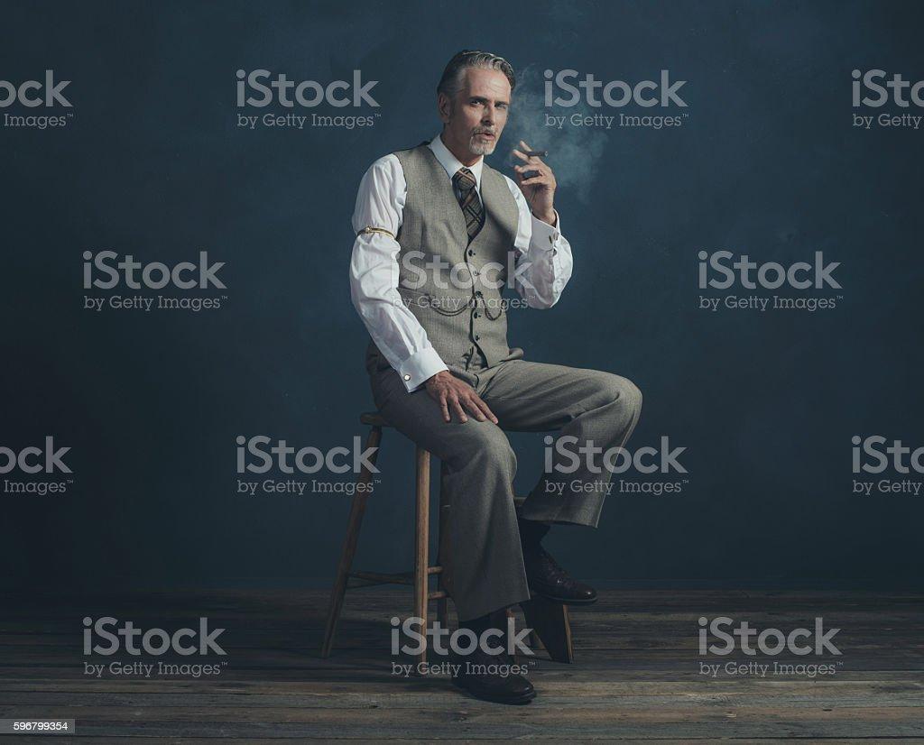 Cigar smoking retro 1920s man sitting on wooden stool. stock photo