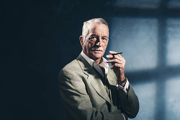 Cigar smoking retro 1940 senior businessman. Studio shot. stock photo