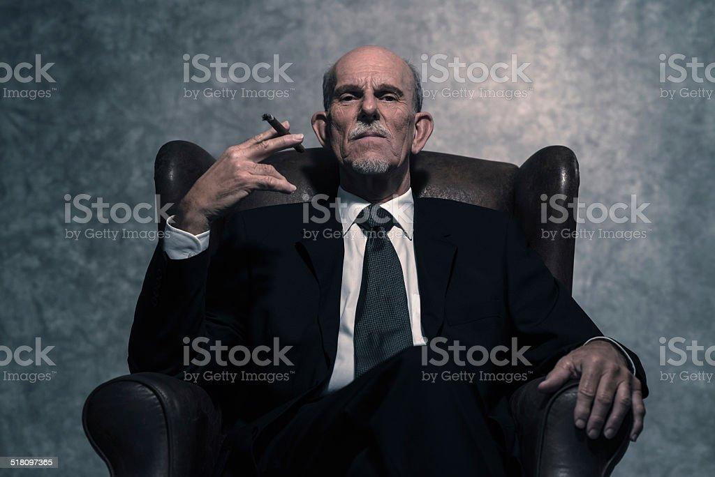 Cigar smoking senior businessman with gray beard wearing dark suit. stock photo