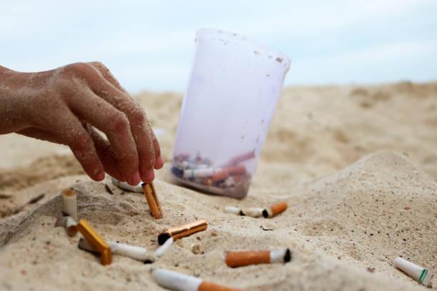 cigarette and tobacco ashtray on the beach - cicca sigaretta foto e immagini stock