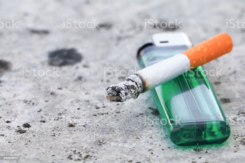 cigarette burn and lighter on floor concrete background. concept Non-smoking day universal stock photo