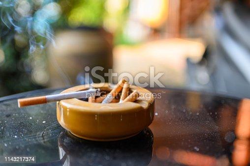 Cigarette burning with smoking on ceramic ashtray
