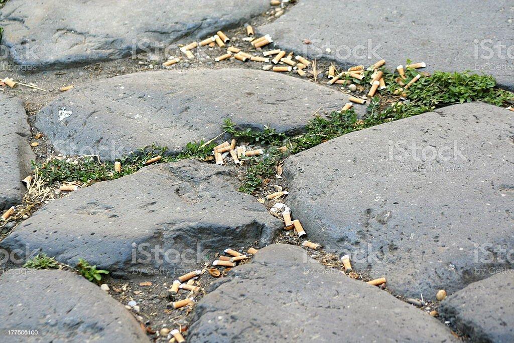 Cigarette butts dropped on cobblestones stock photo
