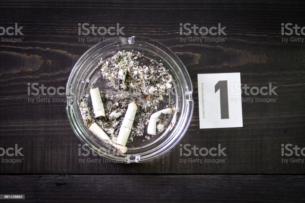 Cigarette butts in an ashtray for DNA analysis stock photo