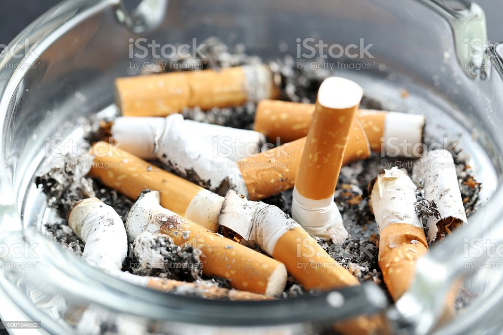 Cigarette butts with ash in ashtray on black background stock photo