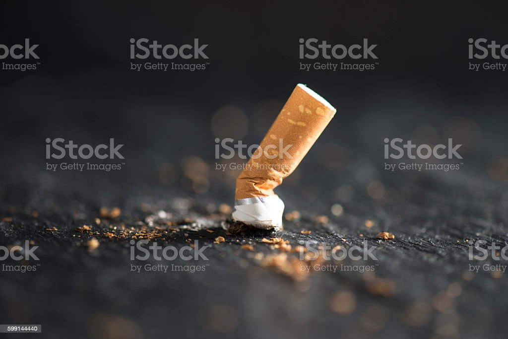 Cigarette End Cigarette butt on abstract background. Addiction Stock Photo