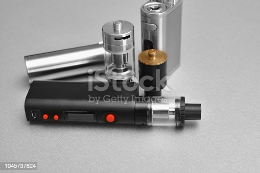 880947556 istock photo E - cigarette for vaping , technical devices.The liquid in the bottle 1045737824