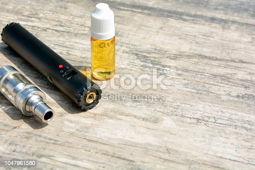 1047961600 istock photo E - cigarette for vaping , technical devices.The liquid in the bottle 1047961580