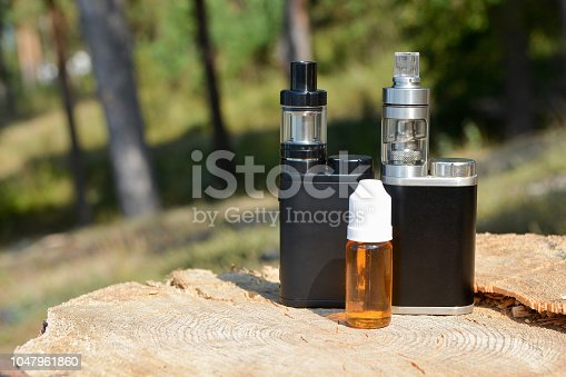1047961600 istock photo E - cigarette for vaping , technical devices.The liquid in the bottle 1047961860