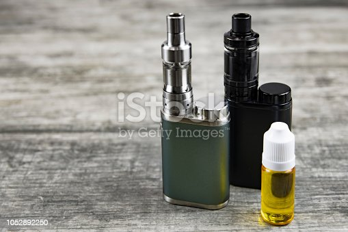 istock E - cigarette for vaping , technical devices.The liquid in the bottle 1052892250