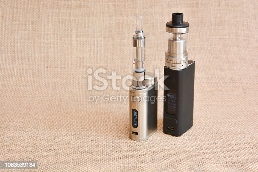 1047961600 istock photo E - cigarette for vaping , technical devices.The liquid in the bottle 1083539134