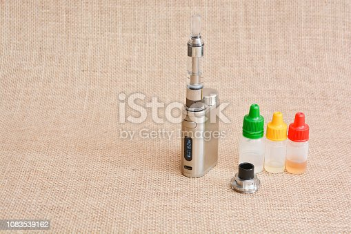 1047961600 istock photo E - cigarette for vaping , technical devices.The liquid in the bottle 1083539162