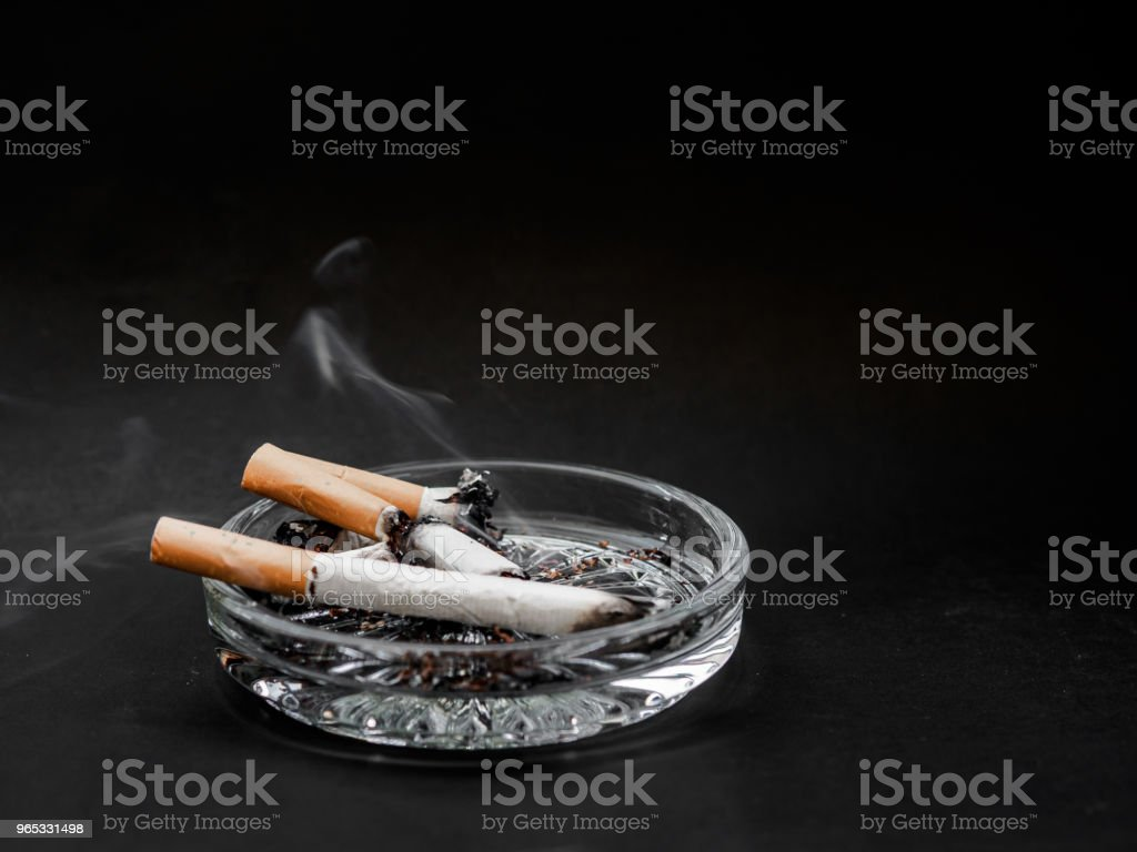 Cigarette in the ashtray on a black background. TOBACCO. royalty-free stock photo