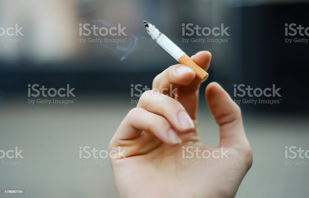 cigarette in the hand stock photo