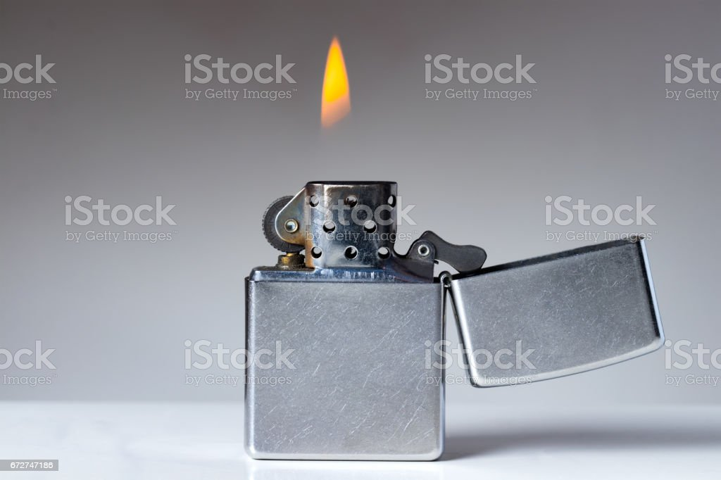 Cigarette lighter with flame on white and grey background. Nicotine and tobacco addiction abstract concept. Copy space on the left. stock photo
