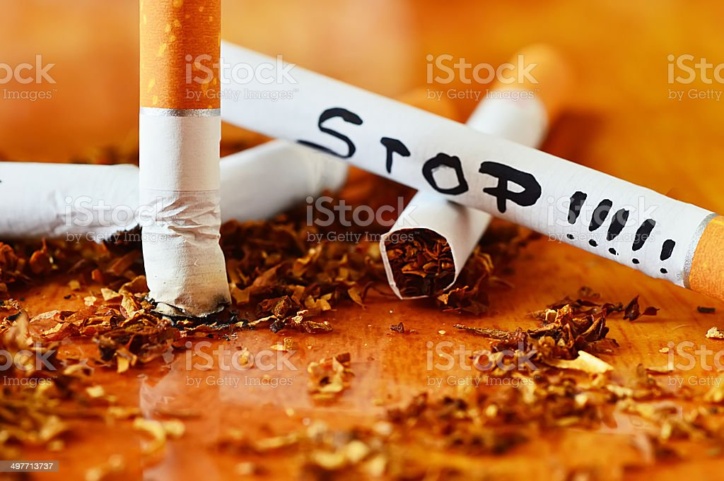 cigarette, tobacco and stop message isolated on wood background stock photo
