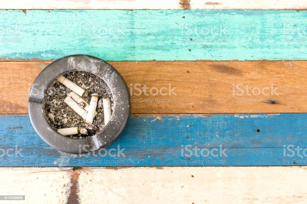 cigarro com um cinzeiro na mesa de madeira. - foto de acervo