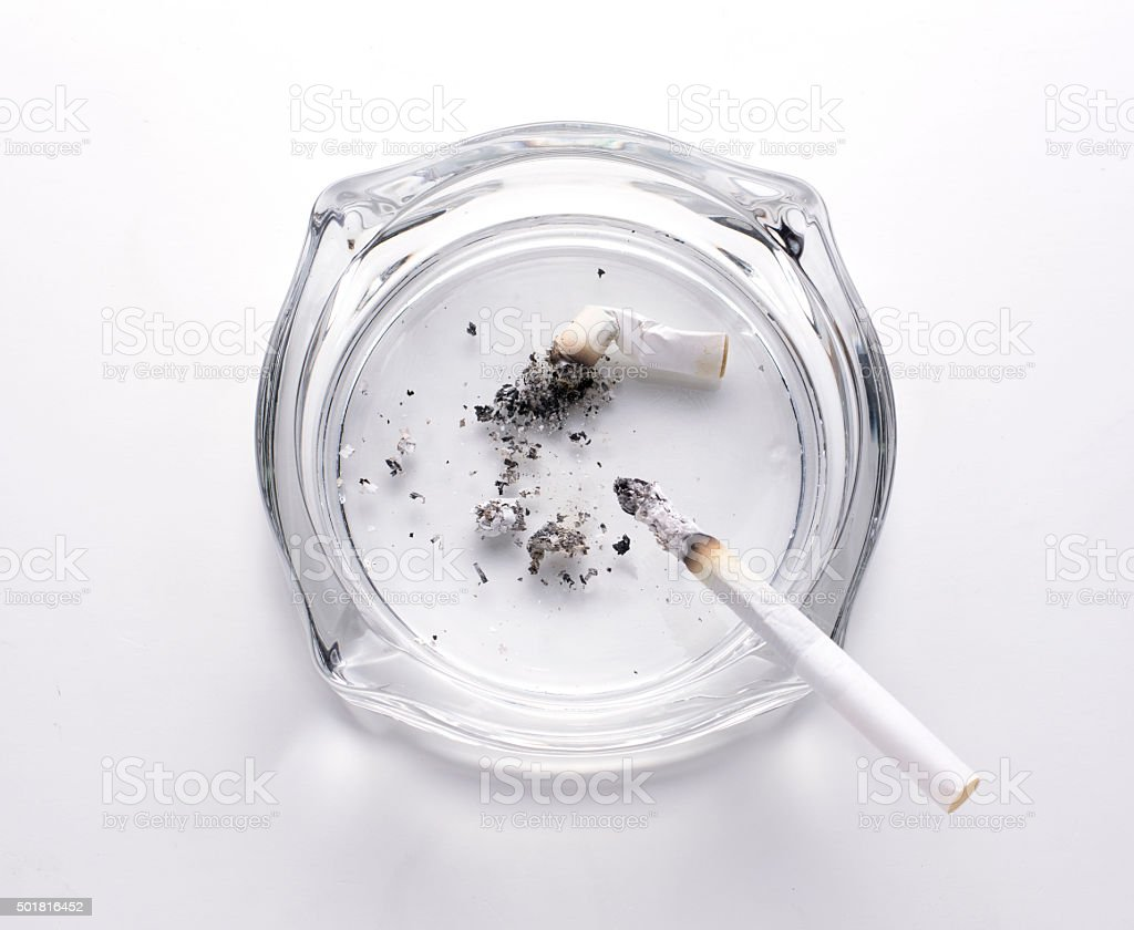 Cigarette with glass ashtray on white backgroud stock photo