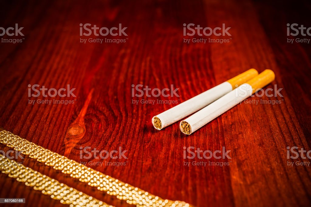 Cigarettes and a gold chain stock photo