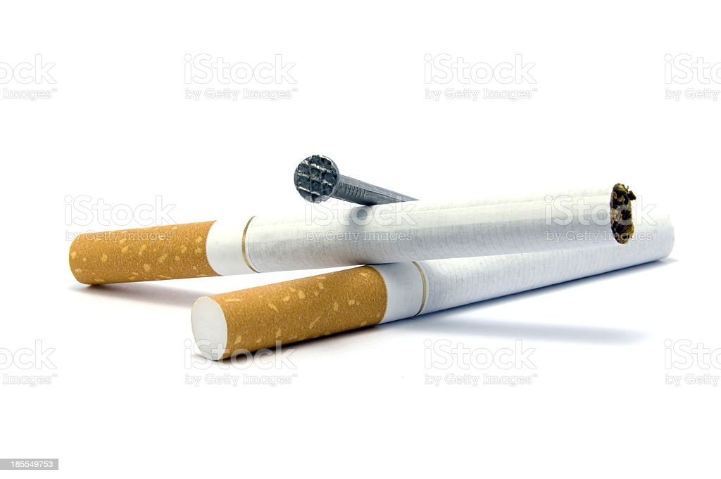 Cigarettes and coffin nail metaphor concept, isolated large macro closeup royalty-free stock photo