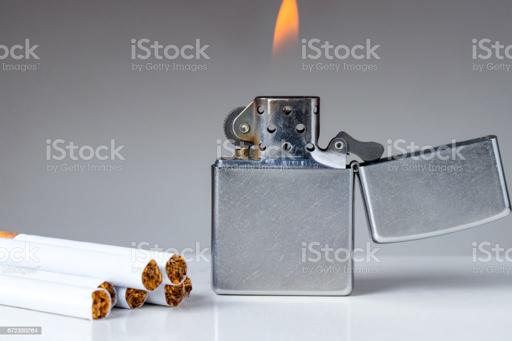 Cigarettes and lighter with flame on white and grey background. stock photo