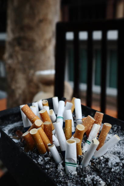 Cigarettes are then left in the ashtray in the smoking area stock photo