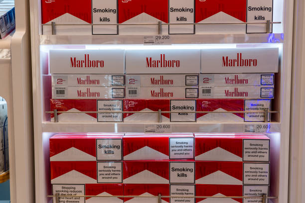 cigarettes department at a duty free segment store with many big packs of marlboro on sale on a shelf in shop airport - cigarettes in duty free foto e immagini stock