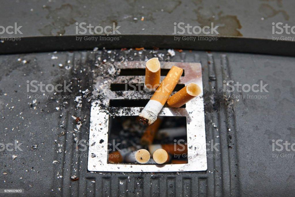 Cigarettes in urban ashtray. Stop addiction. Non healthy lifestyle stock photo