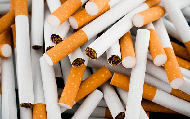 Cigarettes randomly piled in a large heap stock photo