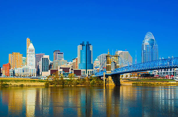 Cincinnati downtown skyline and the John A. Roebling suspension bridge View of the Cincinnati downtown skyline with the John A. Roebling Bridge and the Ohio River in the foreground. cincinnati stock pictures, royalty-free photos & images