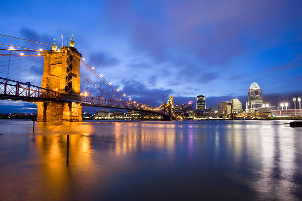 Cincinnati Ohio USA Cityscape of Cincinnati with the Roebling Suspension Bridge leading towards the downtown core and the illuminated Great American Ball Park, home of the Cincinnati Reds. cincinnati stock pictures, royalty-free photos & images