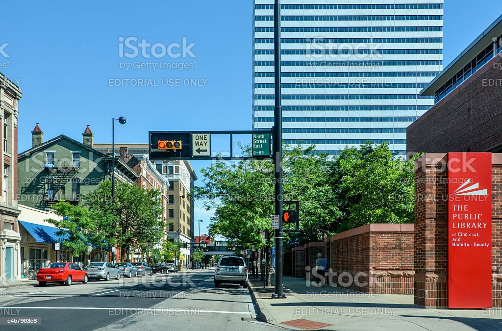 Cincinnati Public Library and Road Cincinnati, USA - June 11, 2016: The Cincinnati Public Library right and a street in Cincinnati, U.S. state of Ohio. A few people of various ages walking on the sidewalk and cars parked up, a few shop signs. Building Exterior Stock Photo