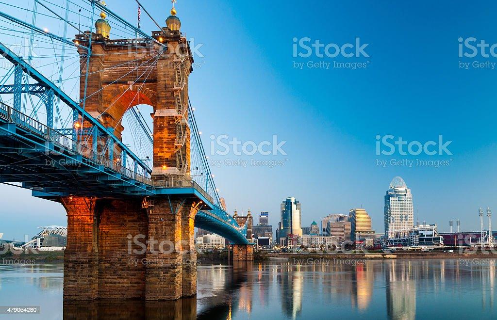 Cincinnati skyline and Roebling Suspension Bridge at dawn Downtown Cincinnati skyline on the right and the Roebling Suspension Bridge on the left, during dawn, as viewed from Covington, Kentucky. 2015 Stock Photo