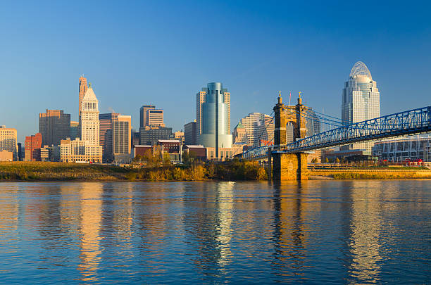Cincinnati Skyline, Bridge, and River in the Morning Downtown Cincinnati skyline during the early morning, with the Ohio River and the Roebling Suspension Bridge in the foreground. cincinnati stock pictures, royalty-free photos & images