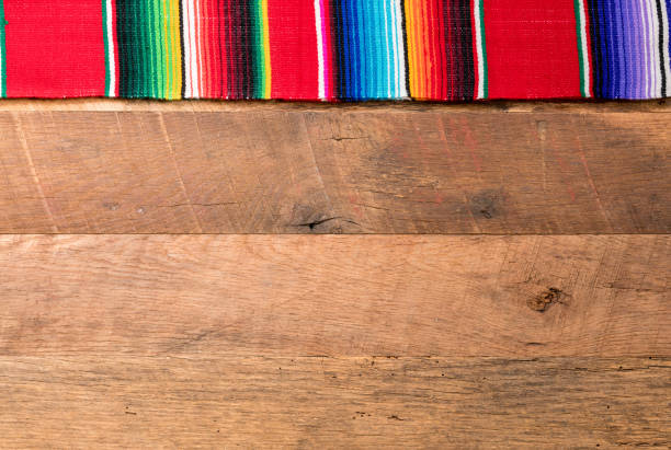Cinco de Mayo background on wooden boards Cinco de Mayo background image on with serape cloth blanket on wooden rustic boards mexican culture stock pictures, royalty-free photos & images
